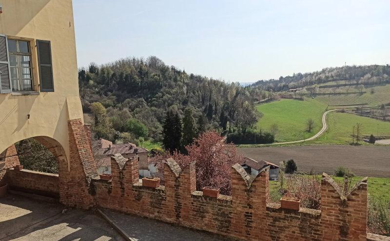 palazzo tornielli e mura esterne con colline Monferrato